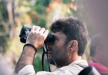 man birding with binoculars in ponta malongane, mozambique