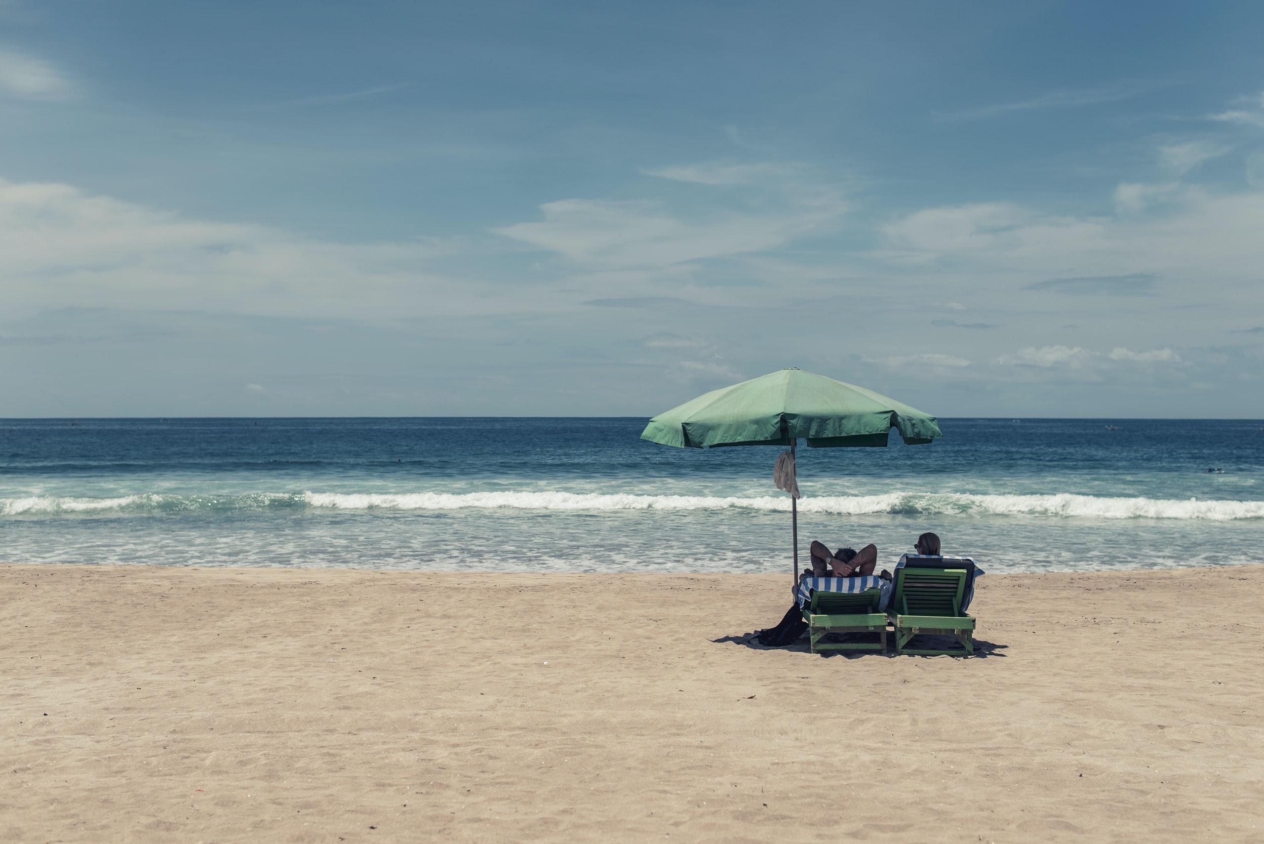 2 people sitting beach chairs under an umbrella on the beach